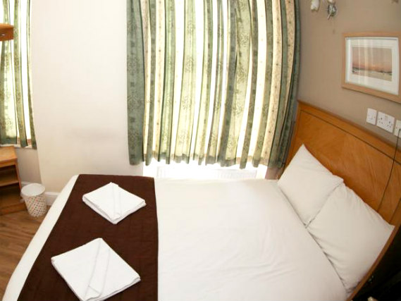 Put your feEin Doppelzimmer im Kensington Suite Hotelet up in front of the TV in your room