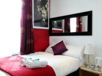 A typical double at Chester Hotel Victoria complete with side table, mirror and towels