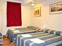 A Quad room with 2 single beds and 1 double bed at Blair Victoria and Tudor Inn Hotel - Perfect for friends or families