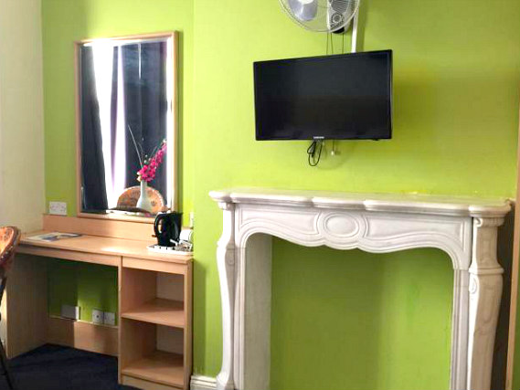 Put your feet up in front of the TV in your room at Euro Lodge Clapham