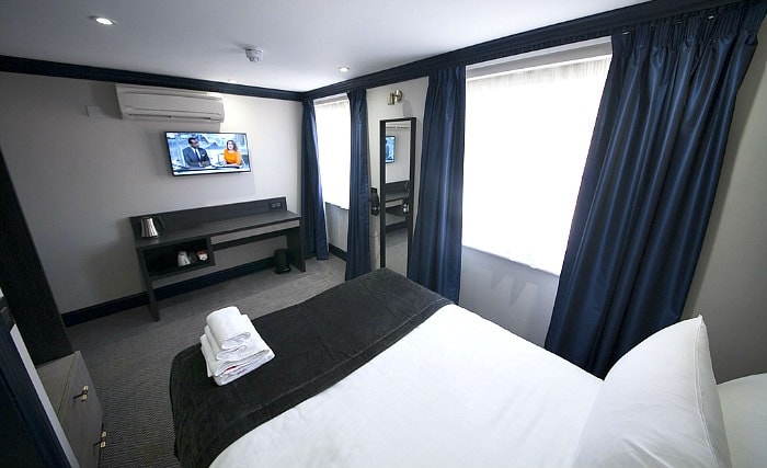 Put your feet up in front of the TV in your room at House of Toby Hotel