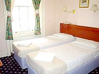 A typical Twin room with private bathroom at Warwick Rooms London