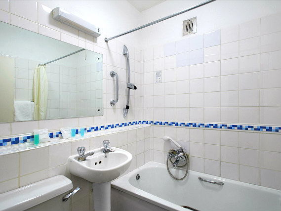 Relax in the private bathroom in your room at Ambassadors Hotel London Kensington