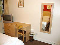 Room including a desk, TV and mirror at City Inn Express s